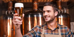 35274508 - happy brewer. happy young male brewer in apron holding glass with beer and looking at it with smile while standing in front of metal containers